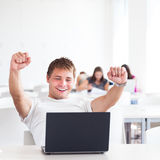 Portrait of a very happy young, male college student. Working on his laptop computer in a classroom/study room/library - expressing joy/success (shallow DOF Stock Photography