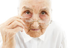 Grandmother with glasses. Portrait of a very old woman taking off her glasses stock photography