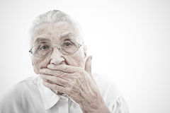 Grandma is mute. Portrait of a very old women  who is masking her mouth with her hand Royalty Free Stock Image