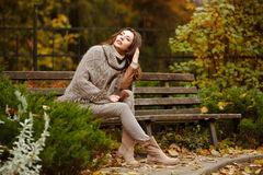 Portrait of a very pretty, smiling girl in a knit sweater, with stock images