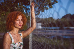 Portrait of a very pretty young woman near a fence. Sunset. Copyspace Royalty Free Stock Image