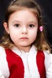 Portrait of very serious baby girl in red santa dress. Borred little santa girl on black background Stock Image