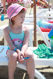 Portrait very serious cute little girl in swimsuit sitting on the beach Stock Photography