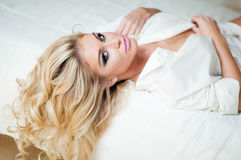 Portrait of a very sexy blonde girl in white shirt lying on the Royalty Free Stock Photos