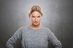 Portrait of a very strict woman is looking at the camera. On a concrete gray background Stock Photo