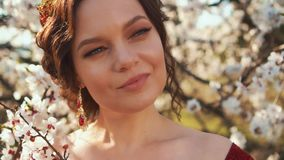 Lady with expensive gold jewelry in red dress, queen with white blooming flowers. Portrait video of adult attractive woman with dark hair and perfect stock footage