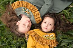 Portrait view from above two girls lie head to head, one looks to the sky another closed her eyes in bliss in retro clothes. Portrait view from above two girls Royalty Free Stock Photos