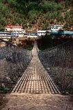 Portrait view of entrance to suspension bridge. Traditional village on the other side. Sagarmatha Everest National Park, Nepal stock images