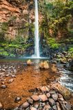 Portrait view of Lone Creek Falls and the red plunge pool. With rocky foreground detail. Mpumalanga, South Africa stock photography