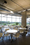 Portrait view offic cafeteria with centered table. Portrait view of office cafeteria in a modern clean building with centered table in focus. Shows a spacious Royalty Free Stock Image