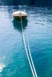 Portrait view of one brown wooden boat tied in the front. Portrait view of one brown wooden boat tied in the front/ Surrounded with a blue sea with small waves Stock Image