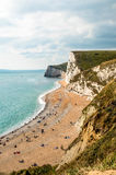 Portrait view of a Rocky Coastline and Beach. The rocky coastline and pebble beach being enjoyed by people on a warm sunny day in summer. Located at Durdle Door Royalty Free Stock Photo