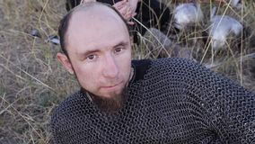 Portrait of a Viking dressed in chain mail lying on the grass stock footage