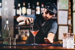 Portrait of vintage bartender working in bar. Pouring and preparing cocktails. Portrait of vintage barman working in bar. Pouring and preparing cocktails royalty free stock images