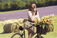 Portrait of vintage pin-up on bike smelling a flower in rural co Stock Photos