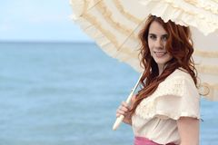 Portrait vintage woman with parasol by ocean. Portrait of smiling vintage woman with parasol by ocean Royalty Free Stock Images