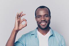 Portrait of virile, harsh, trendy, cheerful, glad man with beami. Ng smile showing ok sign with fingers isolated on grey background Royalty Free Stock Images