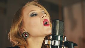 Portrait of vocalist with red lips perform at microphone. Retro style. Make up. Dance. Jazz artist stock video footage