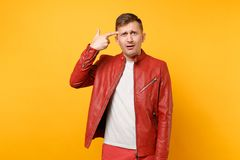 Portrait vogue shocked handsome young man 25-30 years in red leather jacket, t-shirt standing isolated on bright royalty free stock images