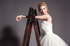Portrait in vogue style of fashion beautiful bride in wedding dr. Ess leaning on wooden ladder on grey background Stock Photography