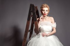 Portrait in vogue style of fashion beautiful bride in wedding dr. Ess leaning on wooden ladder on grey background Royalty Free Stock Photography