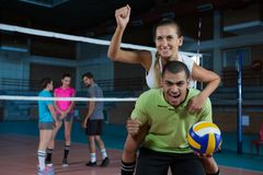 Portrait of volleyball player giving piggyback to teammate Stock Photo