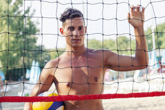 Portrait of volleyball player standing in front of net. At beach Stock Images