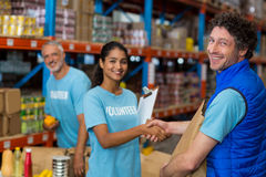 Portrait of volunteers shaking hands while working Stock Image
