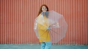 Portrait von hübschen Teenagern in Regenmantel, der Schirm im Freien spinnt und lächelt stock video footage