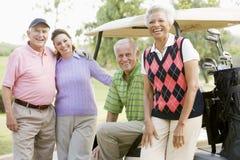 Portrait von vier Freunden, die ein Spiel-Golf genießen Stockbilder