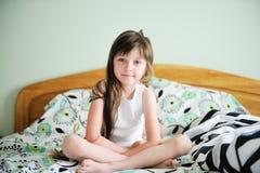 Portrait von wecken das kleine Mädchen, das im Bett sitzt lizenzfreie stockfotos