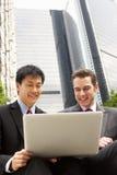 Portrait von zwei Geschäftsmännern, die an Laptop arbeiten lizenzfreie stockfotografie