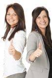 Portrait von zwei Geschäftsfrauen, die sich Daumen zeigen Stockfotografie