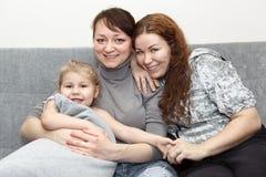 Portrait von zwei glücklichen Erwachsenen und von kleinem Kind Stockbild