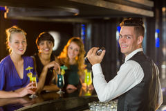 Portrait of waiter and beautiful woman standing at bar counter Stock Image