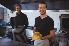 Portrait of waiter with coworker holding food tray in cafe Royalty Free Stock Photos