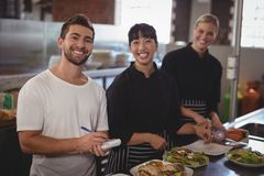 Portrait of waiter with female chefs standing in kitchen. Portrait of waiter with female chefs standing with food in kitchen at cafe Royalty Free Stock Image