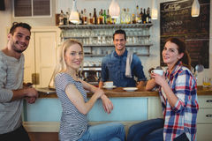 Portrait of waiter with happy customers at cafe. Portrait of young waiter with happy customers at cafe Royalty Free Stock Photography