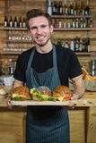 Portrait of waiter holding food at counter Royalty Free Stock Photo