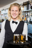 Portrait of waiter holding tray with beer mug Stock Photography