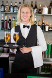 Portrait of waiter holding tray with glasses of beer Stock Images