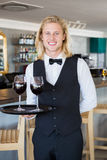 Portrait of waiter holding tray with glasses of red wine Stock Photos