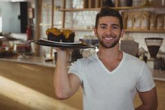 Portrait of waiter holding tray with muffins in cafe. Portrait of smiling young waiter holding tray with muffins in cafe Royalty Free Stock Photo