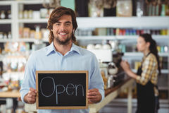 Portrait of waiter showing chalkboard with open sign Stock Image