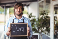 Portrait of waiter showing chalkboard with open sign Royalty Free Stock Photo