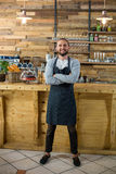 Portrait of waiter standing with arms crossed at counter. In caf Stock Photo
