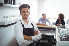 Portrait of waiter standing with arms crossed at counter. In restaurant Stock Images