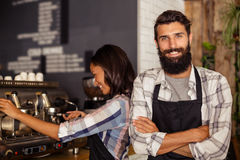 Portrait of waiter standing with arms crossed while waitress working in background. At caf Royalty Free Stock Photos