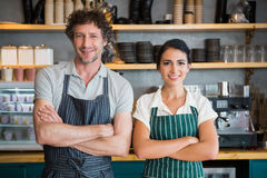 Portrait of waiter and waitress with arms crossed. In cafeteria Stock Photo