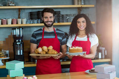 Portrait of waiter and waitress holding a tray of croissants and cake Royalty Free Stock Photography